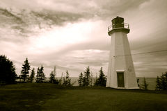 Lighthouse. And trees against cloudy sky (sepia image Stock Images