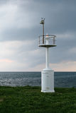 The Lighthouse. A lighthouse on a green meadow with white spring flowers on a background of endless sea and stormy clouds Stock Image