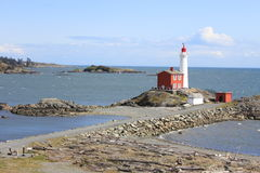 Lighthouse against a blue sky on Vancouver Island. Lighthouse surrounded by sea with a blue sky background on Vancouver Island, British Columbia, Canada royalty free stock image