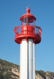 A lighthouse against hill and blue sky background. Detail of the high part of a modern marine lighthouse, red head on white column, with clear blue sky and a Stock Images