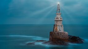 Old white lighthouse tower isolated in calm blue sea water after sunset. Landscape of lighthouse emitting light and rays. Old white lighthouse tower isolated in