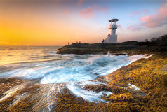 Lighthouse through the air to the sea at night. Royalty Free Stock Images