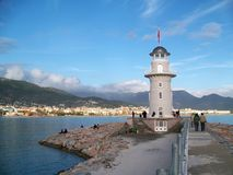 Lighthouse, Alanya, Turkey. Image shows white lighthouse in Alanya, Turkey, with  some tourists in front of the coast, blue sky and some white clouds Stock Images