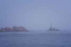 Lighthouse Along Rocky Coastline on Foggy Morning Stock Photo