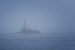 Lighthouse Along Rocky Coastline on Foggy Morning Stock Images