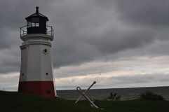 Lighthouse and Anchor on a Stormy Day. A red and white Lighthouse on grass with a white anchor by the water on a stormy day royalty free stock photos