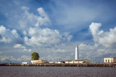 Lighthouse and anchored ships in Kronstadt. KRONSTADT, RUSSIA - AUGUST 23, 2014: Panoramic view from the promenade to the pier with a lighthouse and anchored Stock Image