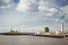 Lighthouse and anchored ships in Kronstadt. KRONSTADT, RUSSIA - AUGUST 23, 2014: Panoramic view from the promenade to the pier with a lighthouse and anchored Royalty Free Stock Image