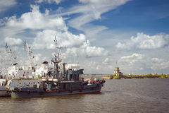 Lighthouse and anchored ships in Kronstadt. KRONSTADT, RUSSIA - AUGUST 23, 2014: Panoramic view from the promenade to the pier with a lighthouse and anchored Royalty Free Stock Photography