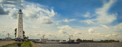 Lighthouse and anchored ships in Kronstadt. KRONSTADT, RUSSIA - AUGUST 23, 2014: Panoramic view from the promenade to the pier with a lighthouse and anchored Royalty Free Stock Images