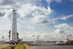 Lighthouse and anchored ships in Kronstadt. KRONSTADT, RUSSIA - AUGUST 23, 2014: Panoramic view from the promenade to the pier with a lighthouse and anchored Royalty Free Stock Photos