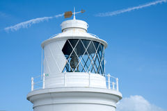Lighthouse with an Arrow Weather Vane. The top of a white lighthouse in Dorset, UK with an arrow shaped weather vane on the roof stock photo