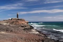 Lighthouse in barren landscape with wild blue sea at north-west tip of Fuerteventura, Canary Islands royalty free stock images