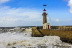Lighthouse battered by huge waves with helicopter on Portuguese Atlantic Ocean. Lighthouse battered by huge waves on Portuguese Atlantic Ocean with helicopter Stock Photo
