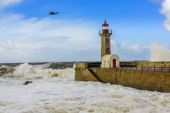 Lighthouse battered by huge waves with helicopter on Portuguese Atlantic Ocean. Lighthouse battered by huge waves on Portuguese Atlantic Ocean with helicopter Stock Photos