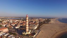 Lighthouse on the beach Praia Velha, Barra, Aveiro, Portugal aerial view stock video