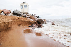 Lighthouse on the beach. Sea waves at a rock . Seahore. Lighthouse on the beach. Sea waves at a rock . Sandy shore. Cloudy sky. Sea foam on the coast stock photography