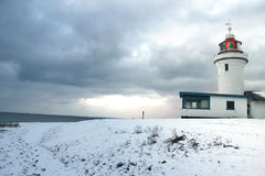Lighthouse beach winter. Lighthouse on beach in the winter. early evening with dark blue skies stock photo