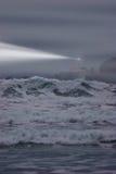 Lighthouse beam cuts through the fog on a stormy evening Stock Photos