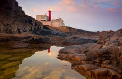 Lighthouse at beautiful sunrise sky and its reflection is in the Stock Images