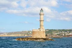 Lighthouse. Beautiful view to the rocky coast with ancient architecture. Seaport touristic town Chania, Creete island, Greece. Turquoise sea with waves royalty free stock image