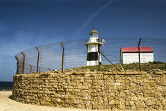 Lighthouse behind fence Stock Images