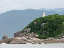 Lighthouse behind the rocky shores of Naufragados, Brazil. Royalty Free Stock Photography