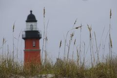 Lighthouse behind Sea Oats in Florida. A red lighthouse stands behind sand dunes and sea oats in Ponce Inlet, Florida, with focus on the sea oats Stock Photos