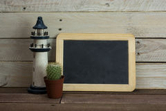 Lighthouse and blackboard against a wood background Royalty Free Stock Photos