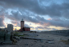 Lighthouse, blue cloudy sky. Dark mood, dramatic blue cloudy sky. Some concrete pieces in the foreground, breakwater at the right. The Baltic Sea Stock Image