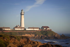Lighthouse and Blue Sky. Scenic view of tall white Pigeon Point lighthouse and buildings in southern California on a cliff with a blue sky background stock photos