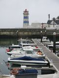 Lighthouse and boats on waterfront Royalty Free Stock Photography