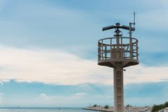 Lighthouse and breakwater formed by concrete blocks Stock Photography