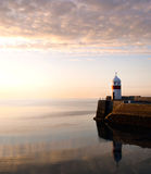 Lighthouse on breakwater wall with calm sea Stock Photography