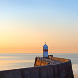 Lighthouse on breakwater wall during sunrise Stock Images