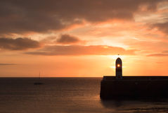 Lighthouse on breakwater wall during sunrise Stock Image