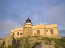 Lighthouse built on a building at sunset Stock Photography
