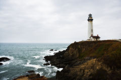 Lighthouse in California. A Lighthouse on top of a cliff above the waves hitting the shore at the pacific coast along highway 1 in California Stock Photo