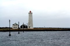 Lighthouse in a calm and cloudy day. stock photos