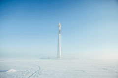 Lighthouse in a calm and desolate winter landscape. A white whitewashed lighthouse  over blue sky with clouds Stock Photo