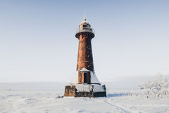 Lighthouse in a calm and desolate winter landscape. A white whitewashed lighthouse  over blue sky with clouds Royalty Free Stock Photo