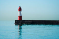 Lighthouse on calm sea. Red and white lighthouse on jetty on calm sea Stock Photos