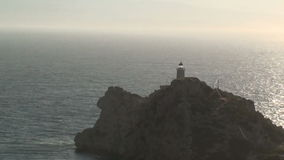 Lighthouse at cape. A big lighthouse on the rocks of a cape during a sunny afternoon - zoom out stock footage