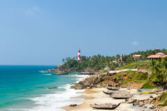 The lighthouse on the cape stretching into the Arabian Sea, beach and fishing boats. At a resort in Kerala in sunny weather Stock Images