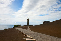 Lighthouse Capelinhos on the shore of Atlantic ocean, island Fai Stock Images