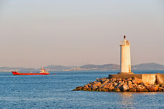 Lighthouse & cargo ship Stock Images