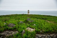 Lighthouse centered on the background of the sea in cloudy weather. Lighthouse in the center of the frame. In the foreground are grass and stones stock images