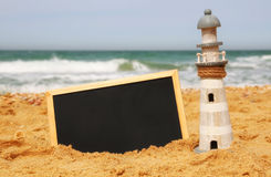 Lighthouse and chalkboard, on sea sand and ocean horizon Royalty Free Stock Photography