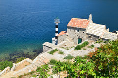 Lighthouse with Church in the Bay of Kotor, Montenegro. Stone-built lighthouse, serene blue sea and green fig trees. Bay of Kotor, Montenegro Stock Photos