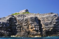 The lighthouse on an cliff. The house of the lihgthouse keeper on the Sv. Nikola Island, Montenegro Stock Photo